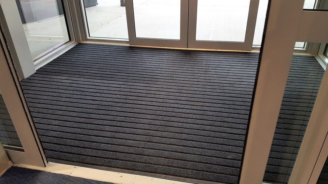 Black coloured entry matting, installed into a wind lobby