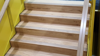 Freedom Strategies installed Stepmaster  stair inserts SMI501 Silver Anodised at Aurecon specified by Warren and Mahoney (WAM), on wooden timber stair.